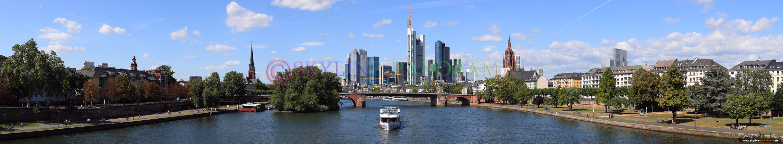 Panorama Bild - Die Frankfurter Skyline mit einem Ausflugsschiff von der Ignatz-Bubis-Brücke am Tag gesehen.