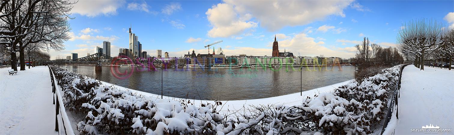 Panorama Bild vom verschneiten Sachsenhäuser Mainufer auf den Eisernen Steg mit der dahinterliegenden Skyline und dem Kaiserdom Frankfurts.