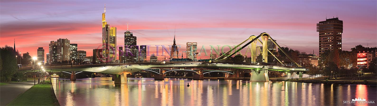 Dieses Panorama zeigt die Flößerbrücke und die dahinter liegende Skyline von Frankfurt am Main. Die Aufnahme entstand in Frankfurt während des Sonnenuntergangs