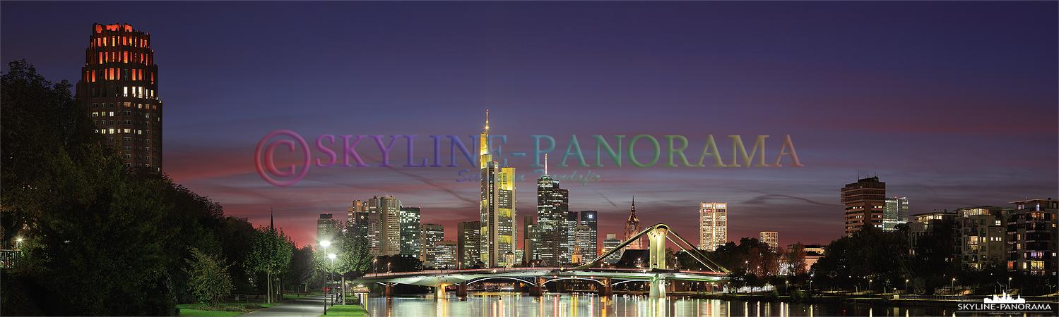 Panorama der Skyline von Frankfurt am Main kurz nach dem Sonnenuntergang. Die Aufnahme entstand in der Blauen Stunde und zeigt den Blick vom Deutschherrnufer