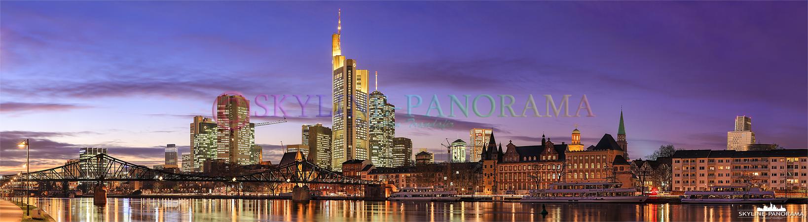 Panorama Bild Frankfurt am Main – Die abendlich beleuchtete Skyline von Frankfurt a. M. zusammen mit dem historischen Eisernen Steg im Vordergrund vom Mainufer in Frankfurt Sachsenhausen gesehen. Das Panorama ist kurz nach dem Sonnenuntergang, in der Dämmerung, bei einbrechender Nacht entstanden.