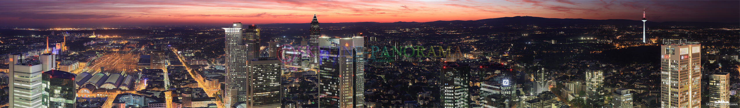 Ein Panorama, das kurz nach dem Sonnenuntergang entstanden ist und den glutroten Himmel über den Bankentürmen der Frankfurter City zeigt - der Ausblick geht in Richtung Westen, über den Hauptbahnhof, die Frankfurter Messe bis hinauf in den Taunus mit dessen höchster Erhebung, dem Feldberg.