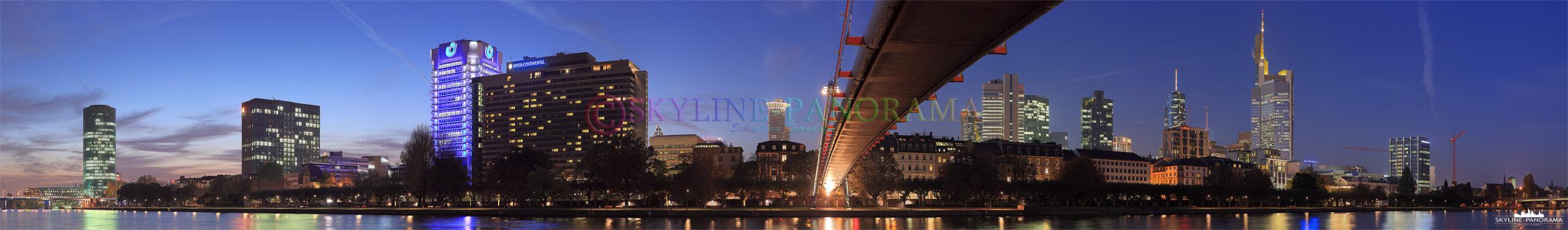Die Skyline der internationalen Bankenstadt Frankfurt vom abendlichen Mainufer aus gesehen, der Blick zur Blauen Stunde geht unter dem Holbeinsteg ...