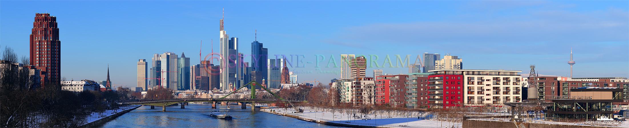 Skyline Bilder - Das Panorama zeigt den Blick von der Deutschherrnbrücke auf die verschneite Frankfurter Skyline mit den bekannten Hochhaustürmen.