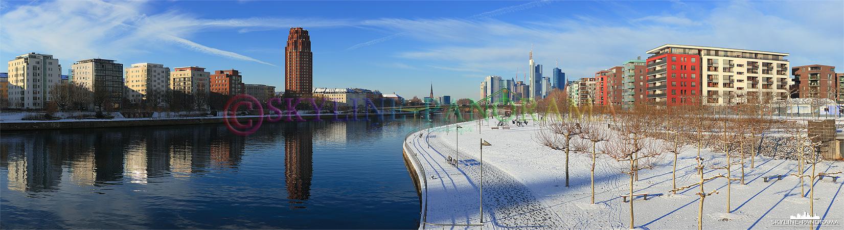 Winterbilder Frankfurt - Das verschneite Mainufer im Osten von Frankfurt mit Blick auf das Mainplaza und ein Teil der Frankfurter Skyline.