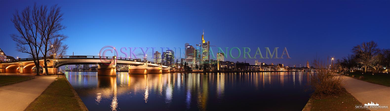 Bilder aus Frankfurt - Das Abendliche Panorama der Frankfurter Skyline zur Blauen Stunde mit der Untermainbrücke vom Mainufer aus gesehen.