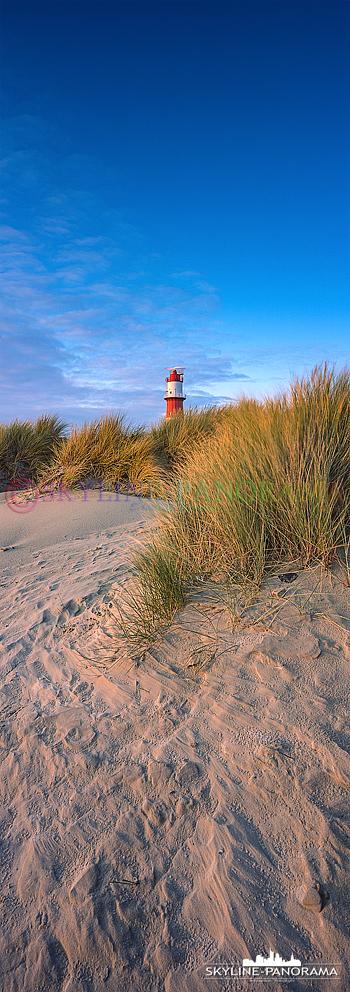 Die Dünen am Südstrand von Borkum mit dem elektrische Leuchtturm als hochkant Panorama im letzen Sonnenlicht des Tages.