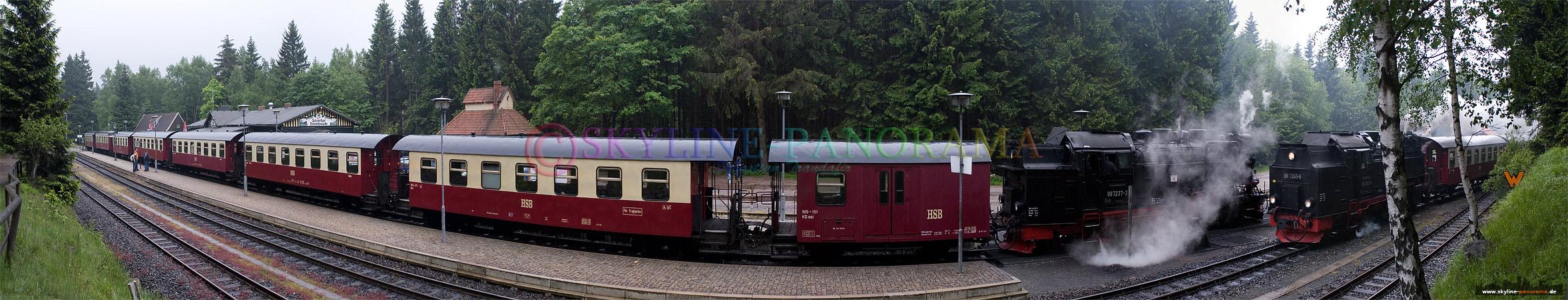 Bahnhof Schierke mit der einfahrenden Brockenbahn und einem stehenden Zug der auf die Weiterfahrt auf den Berg wartet.