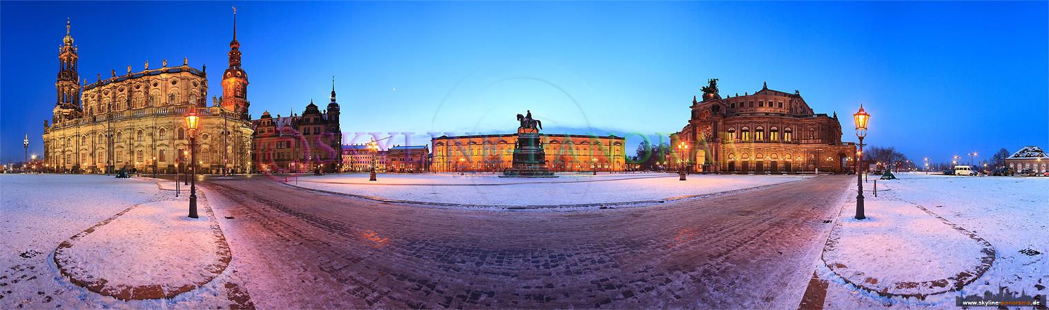 Dresden im Winter - Der verschneite abendliche Theaterplatz von Dresden mit der Hofkirche, dem Hausmansturm, der Gemäldegalerie und dem bekanntesten Opernhaus Deutschlands, der Semperoper.