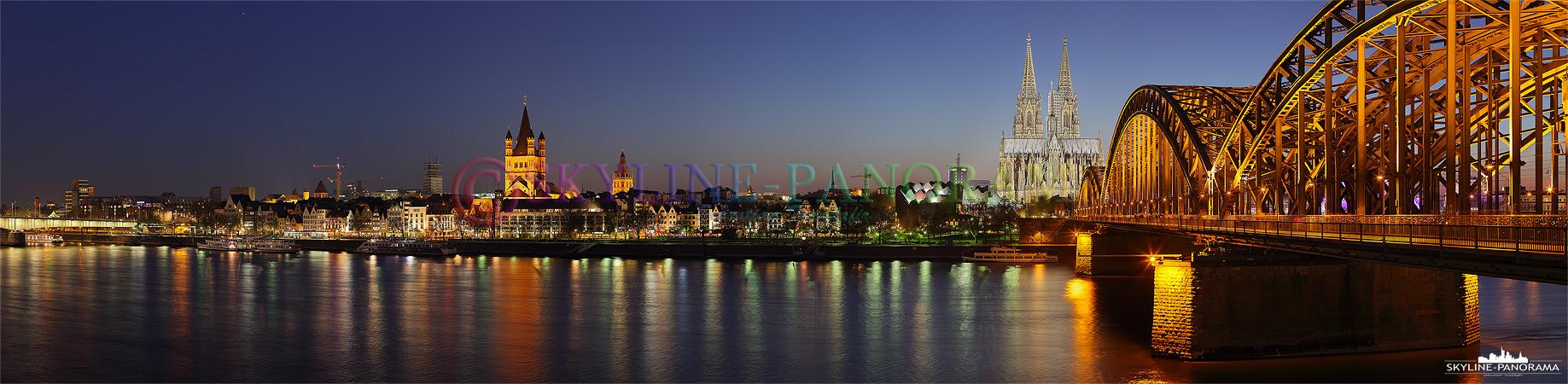 Köln Skyline - Panorama Bild vom Sockel der Hohenzollernbrücke in der Dämmerung. Entstanden ist das Skyline Bild im April 2010 als über Deutschland eine Aschewolke des Isländischen Vulkans Eyjafjallajökull den Flugverkehr behinderte und den Fotografen fotogene Sonnenuntergänge frei von Flugzeugen bescherte.