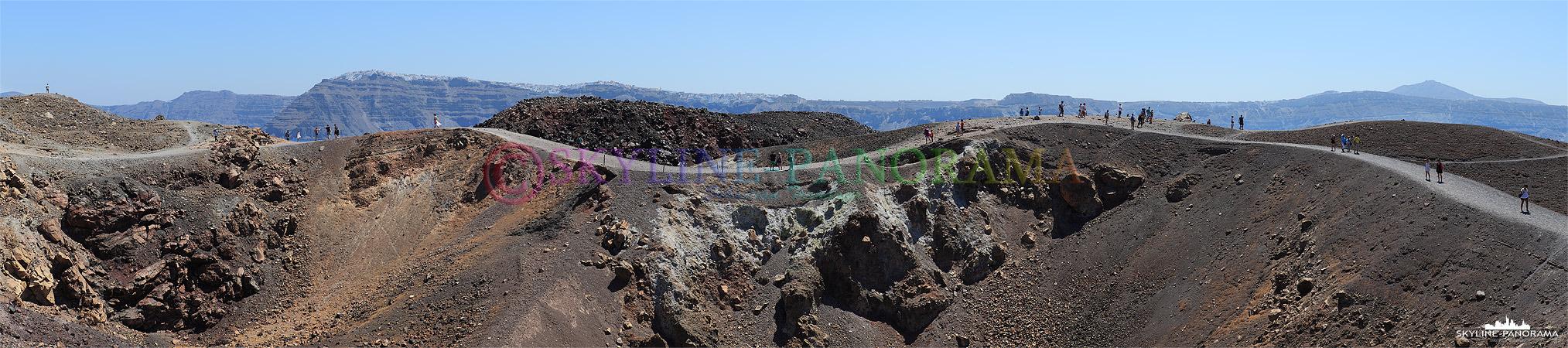 Der Vulkan von Santorini; im Vordergrund kann man die Schwefeldämpfe des ruhenden Kraters beobachten, im Hintergrund sieht man den Ort Fira auf der Hauptinsel.