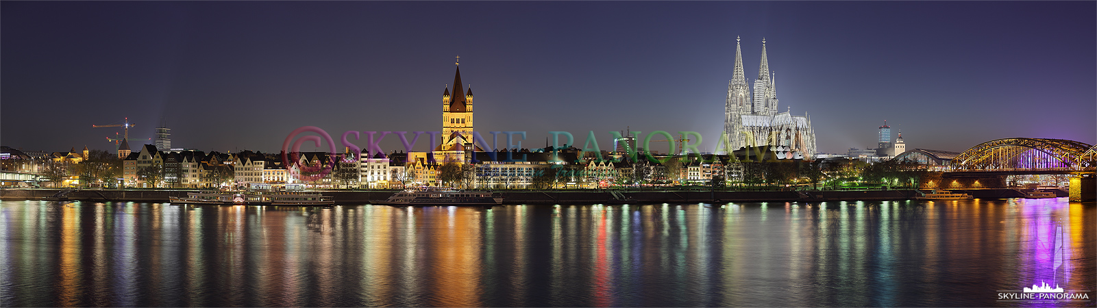 Panorama der abendlichen Kölner Skyline mit dem beleuchteten Kölner Dom und der Kirche Sankt Martin.