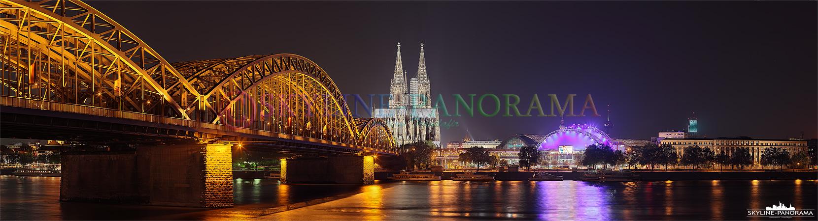 Die Kölner Skyline mit der Hohenzollernbrücke, dem Kölner Dom und dem Musical Dome bei Nacht vom Rheinufer aus gesehen.