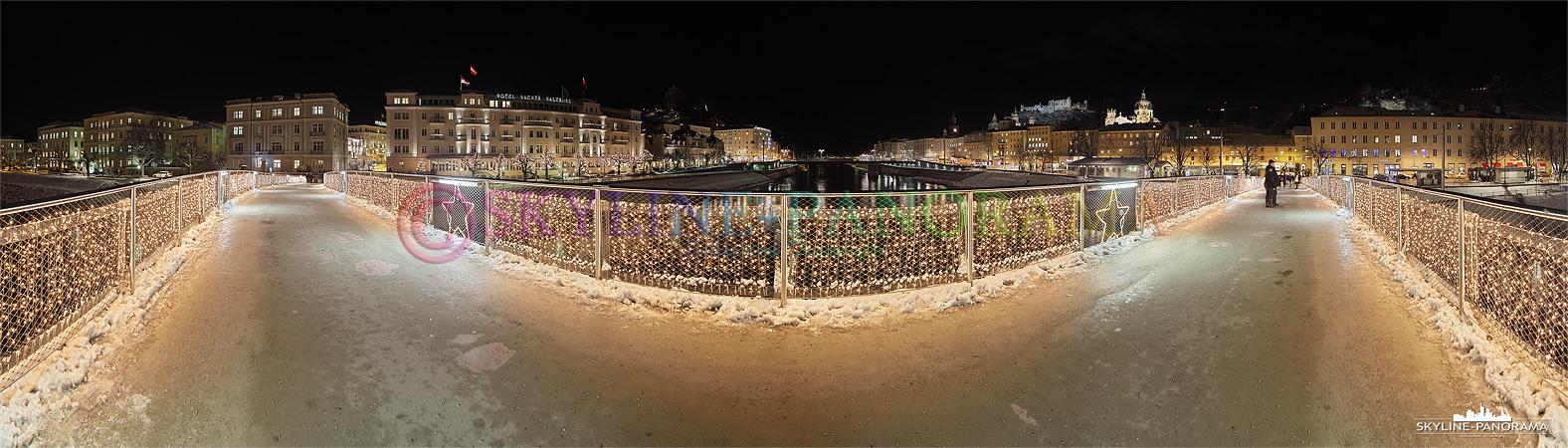 Bilder aus Österreich - Panoramablick vom weihnachtlich geschmückten Makartsteg über die Salzach in Salzburg, die Aufnahme wurde am Abend erstellt.