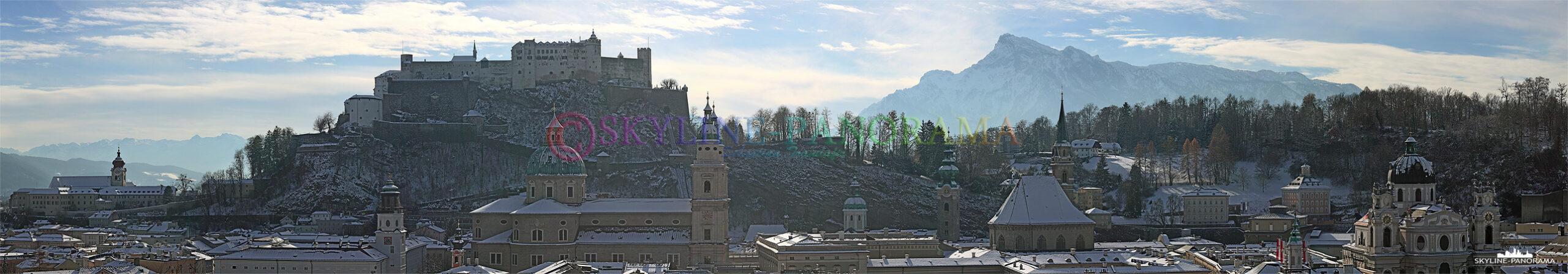 Die verschneiten Dächer der Altstadt von Salzburg mit der Festung Hohensalzburg und dem dahinter liegenden Untersberg.