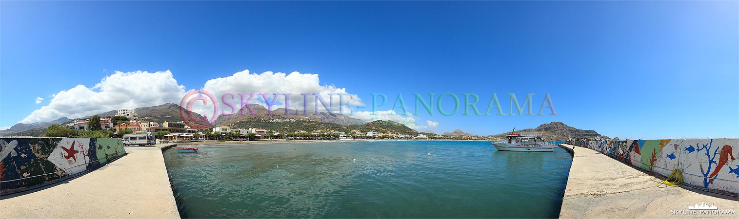 Das Panorama zeigt den Blick aus dem Fischerhafen von Plakias mit dem langen Sandstrand und den Berghängen, die unmittelbar hinter dem Ort aufsteigen.