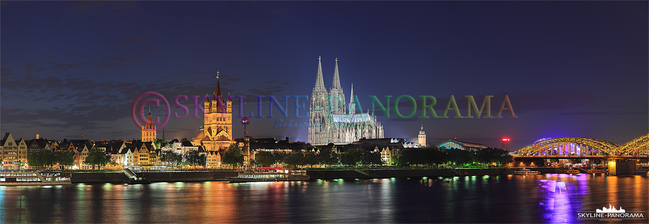 Die Kölner Skyline am Rheinufer vom Sockel der Deutzer Brücke aus gesehen. Das Köln Panorama zeigt den Rathausturm, die Kirche Sankt Martin und den Kölner Dom bei abendlicher Beleuchtung.