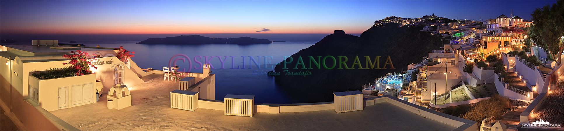 Ausblick von Firostefani auf die Caldera von Santorini kurz nach dem Sonnenuntergang, im Vordergrund ist die bekannte Terrasse des Galini Cafes zu sehen.