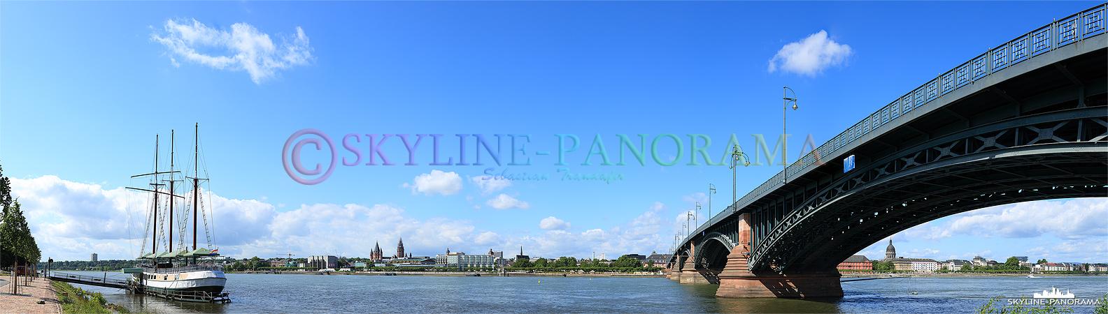 """Skyline Bild - Stadtansicht der Mainzer Skyline mit dem Restaurantschiff """"Pieter van Aemstel"""" und der Theodor-Heuss-Brücke vom Rheinufer aus gesehen."""