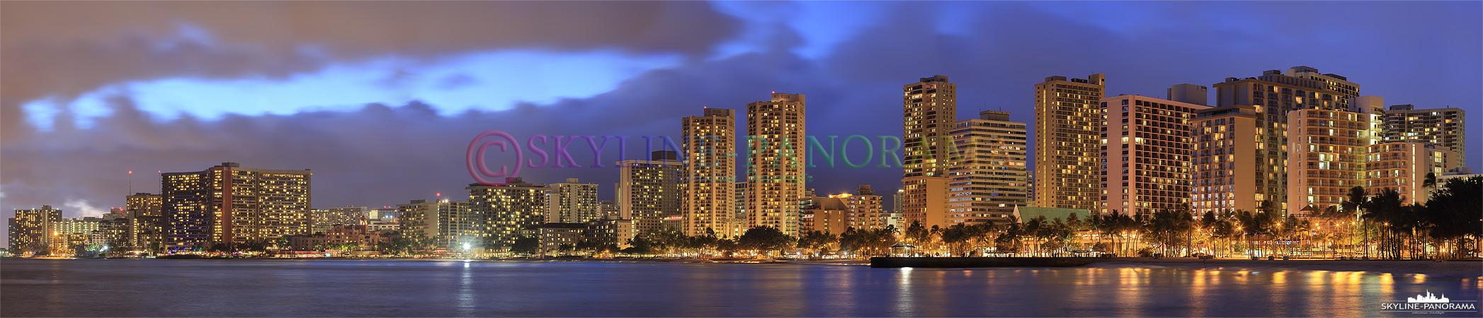 Die Skyline von Honolulu mit zahlreichen Hotels und Hochhäusern im Stadtteil Waikiki - zu sehen ist der Traumstrand mit seiner Promenade als Panorama nach Sonnenuntergang.