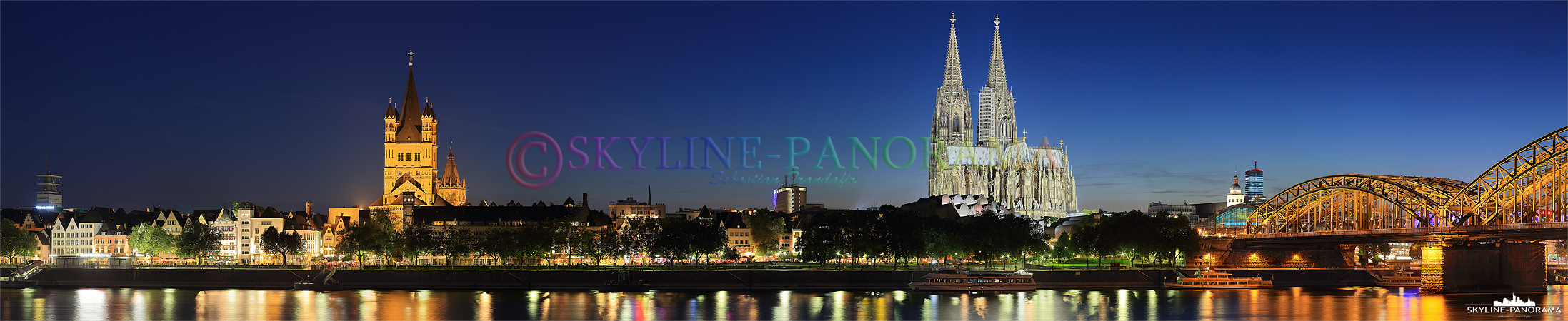 Panorama mit Kölner Dom - Die abendlich beleuchtete Skyline der Domstadt Köln - das Bild zeigt das Panorama vom Rheinufer aus auf die Kölner Altstadt mit der Kirche Sankt Martin und dem Kölner Dom zur einbrechenden Nacht.