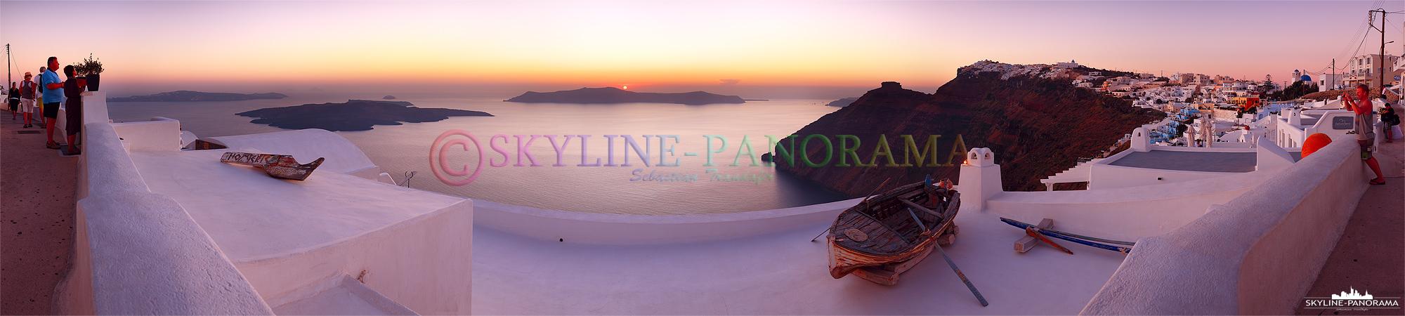 Das Boot im Vordergrund gehört zu den beliebtesten Motiven auf Santorini. Das Panorama zeigt den Blick mit den Fischerboot zum Sonnenuntergang in Firostefani.