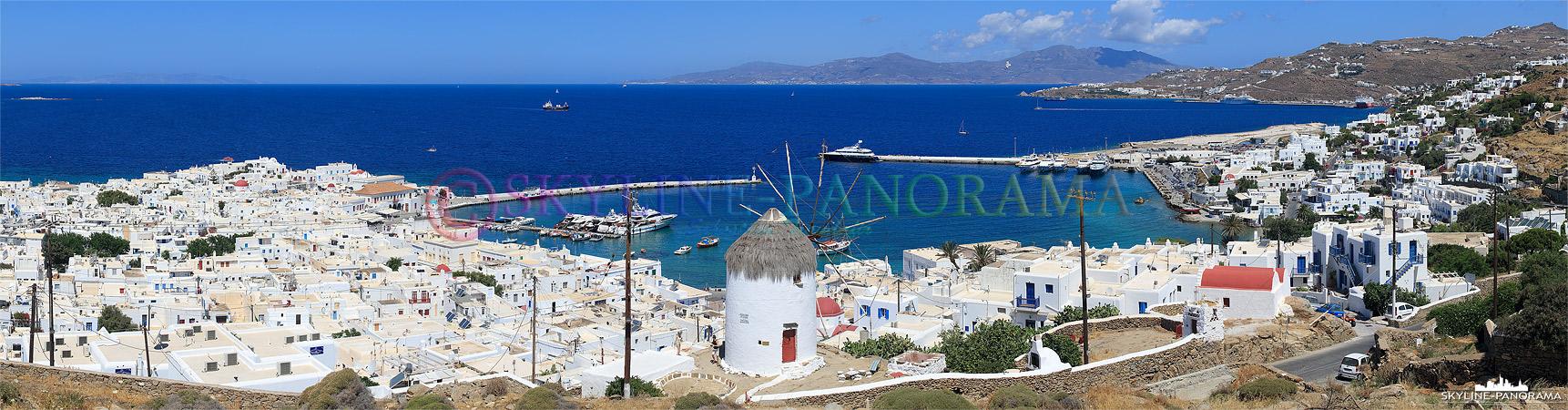 Panorama von dem oberhalb der Chora, auf dem Weg nach Ano Mera, gelegenen Aussichtspunkt auf die Windmühle Ano Myli und den Alten Hafen von Mykonos Stadt.