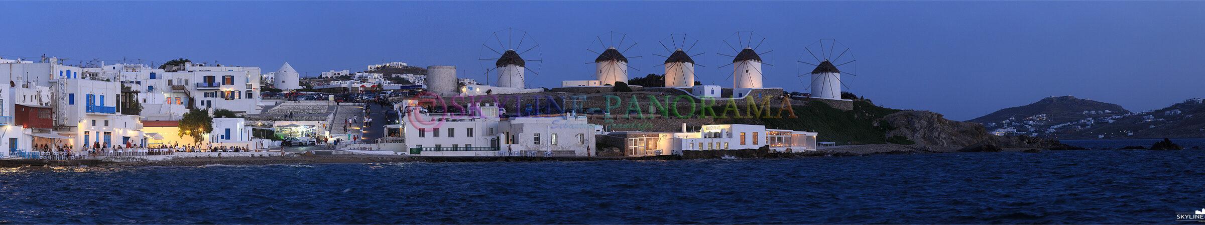 Die als Kato Myli bekannten 5 Windmühlen von Mykonos sind nach Sonnenuntergang zu sehen, Restaurants im Alefkandra Viertel bewirten ihre Gäste direkt am Wasser