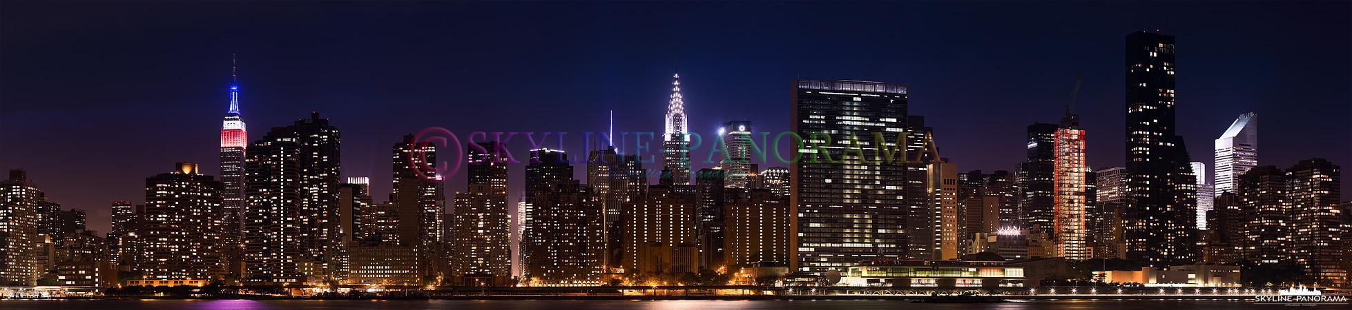 NYC zur Nacht - Die Skyline von Manhattan gesehen vom Gantry Plaza State Park in Queens, von diesem Aussichtspunkt hat man ein fantastisches Panorama auf Midtown mit den zwei bekannten Towern Empire State Building und Chrysler Building.