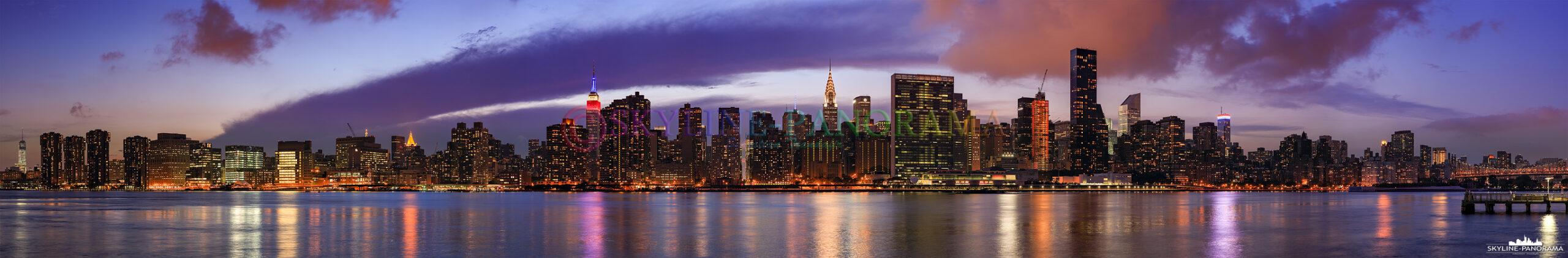 Panorama Manhattan - Die abendliche Skyline von Manhattan Midtown vom Gantry Plaza State Park in NY Queens gesehen. Von diesem Aussichtspunkt aus hat man einen fantastischen Blick auf die bekanntesten Wolkenkratzer von New York City – zum Beispiel das in den US - Nationalfarben Rot, Blau und Weiß beleuchtete Empire Sate Building, den Feedom Tower und das Chrysler Building - um nur einige zu nennen.