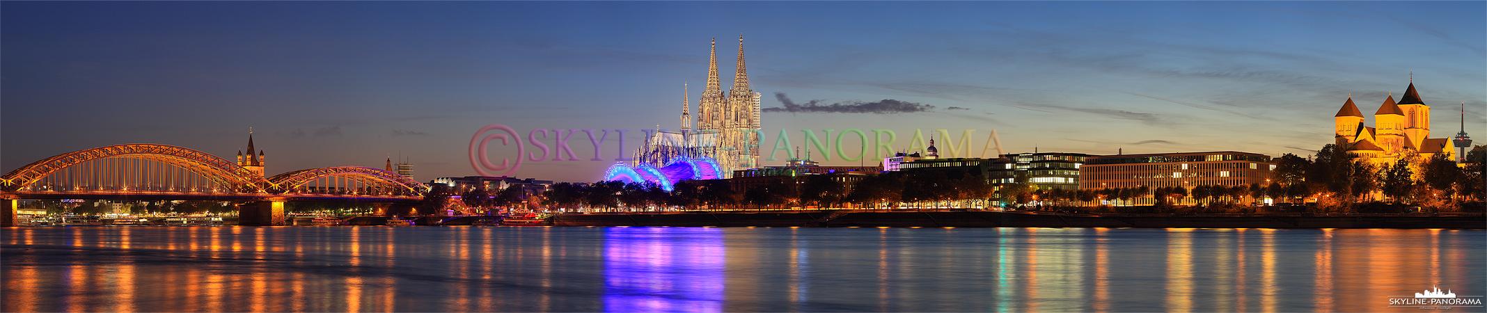 Skyline vom Rheinufer - Panorama der Kölner Skyline in der Blauen Stunde, der Blick geht links beginnend, von der Hohenzollernbrücke mit der dahinter liegenden Kirche Groß Sankt Martin, zum Kölner Dom, dem Konrad-Adenauer-Ufer, bis hin zum Kunibertskloster.