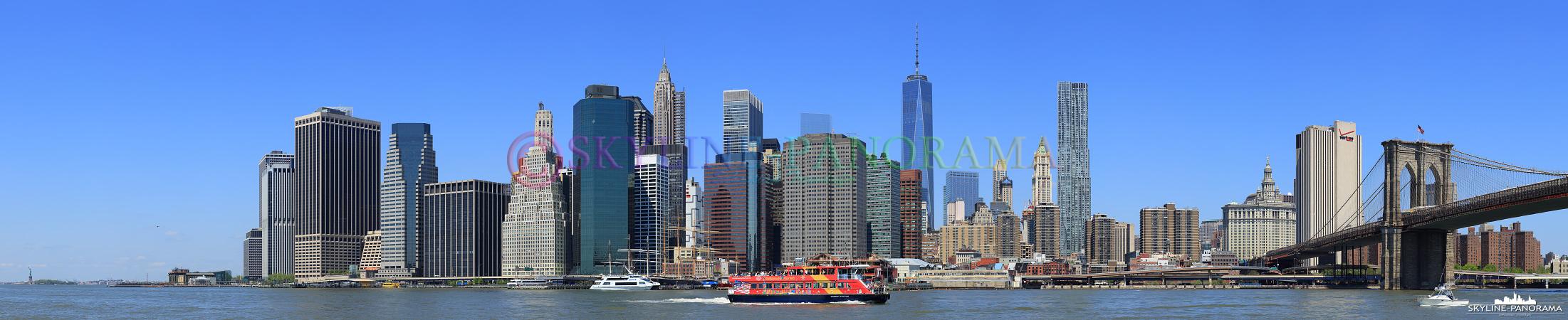 Skyline von Manhattan - Dieses Panorama entstand am Tag, vom Brooklyn Bridge Park im New Yorker Stadtteil Brooklyn, es zeigt die Südspitze von Manhattan, auch als Finanzdistrikt bezeichnet, mit der Brooklyn Bridge, dem One World Trade Center 1 und am linken Bildrand - relativ klein - die Freiheitsstatue.