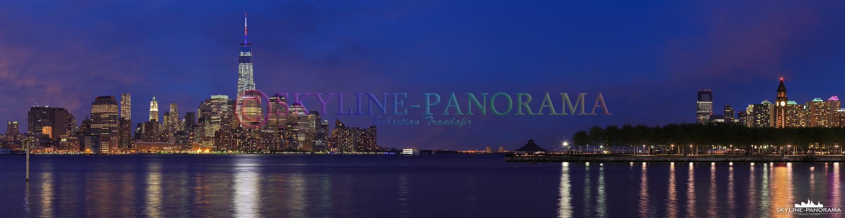 Bilder New York - Die hell erleuchtete Skyline von Lower Manhattan in der Dämmerung mit dem Financial District und einem Teil der Pieranlagen von Hoboken, New Jersey.