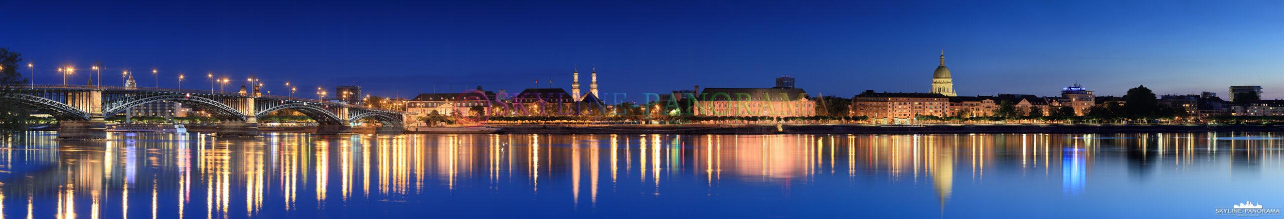 Die Stadtansicht von Mainz, der Landeshauptstadt des Bundeslandes Rheinland-Pfalz, zur Blauenstunde mit einem spiegelglatten Rhein von Mainz-Kastel aus gesehen.