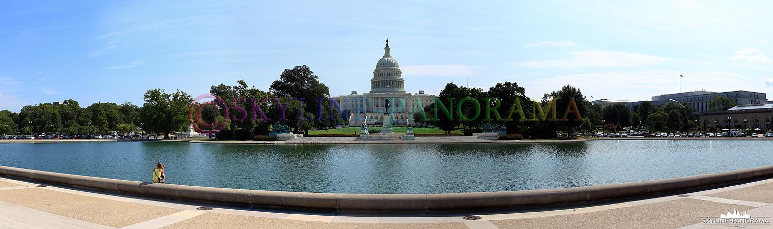 Sehenswürdigkeiten in Washington - Das U.S. Capitol mit dem Capitol Reflecting Pool im Vordergrund als Panorama am Tag.