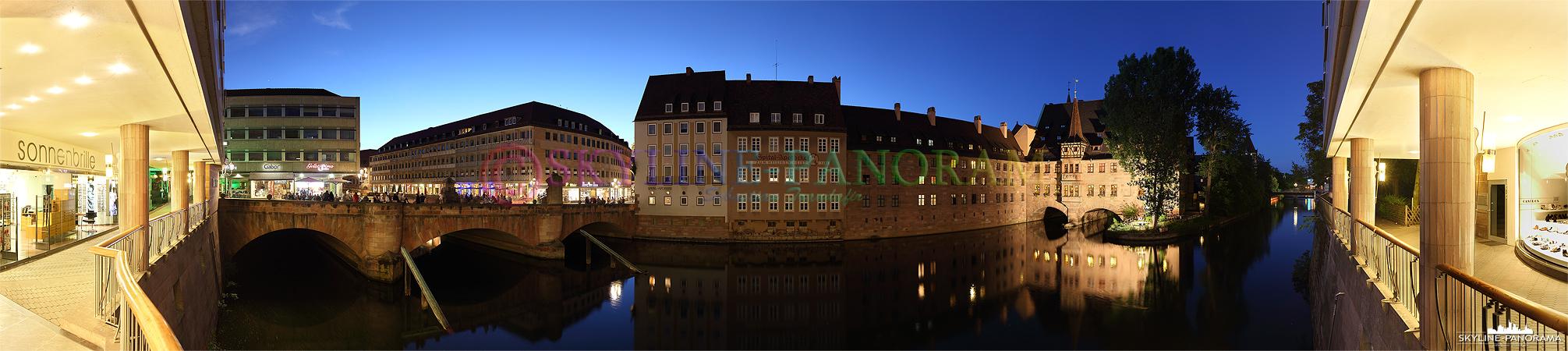 Sehenswürdigkeiten Nürnberg - Das abendliche Panorama auf eine der bekanntesten Sehenswürdigkeiten von Nürnberg - das beleuchtete Heilig Geist Spital mit der Spital-Apotheke an der Pegnitz gelegen.