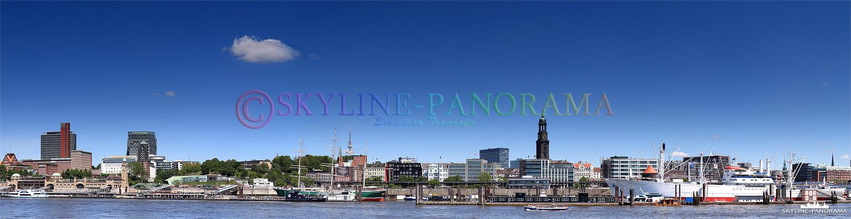 Panorama auf die Landungsbrücken der Stadt Hamburg mit dem Blick auf den Pegelturm, die historischen Schiffe Rickmer Rickmers und Cap San Diego, sowie die Sankt Michaelis Kirche.