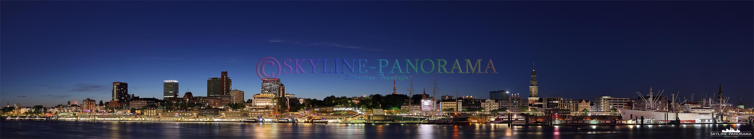 """Das Panorama der Hamburger Skyline zur Blauen Stunde mit dem Blick auf die als Landungsbrücken, von hier aus fahren Ausflugsboote zur """"Großen Hafenrundfahrt""""."""