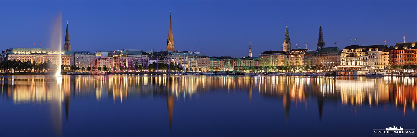 Bilder aus Hamburg – Das Hamburger Alster Panorama zur Blauen Stunde mit dem Blick auf die Alsterfontäne und den beleuchteten Jungfernstieg.