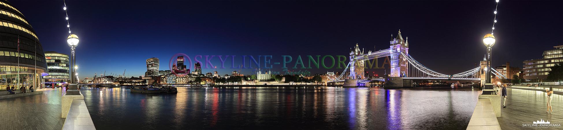 Blick auf die Londoner Skyline mit dem abendlich erleuchteten Tower von London und der historischen Tower Bridge, dieses Panorama ist an der The Queen´s Walk genannten Promenade der Themse entstanden.