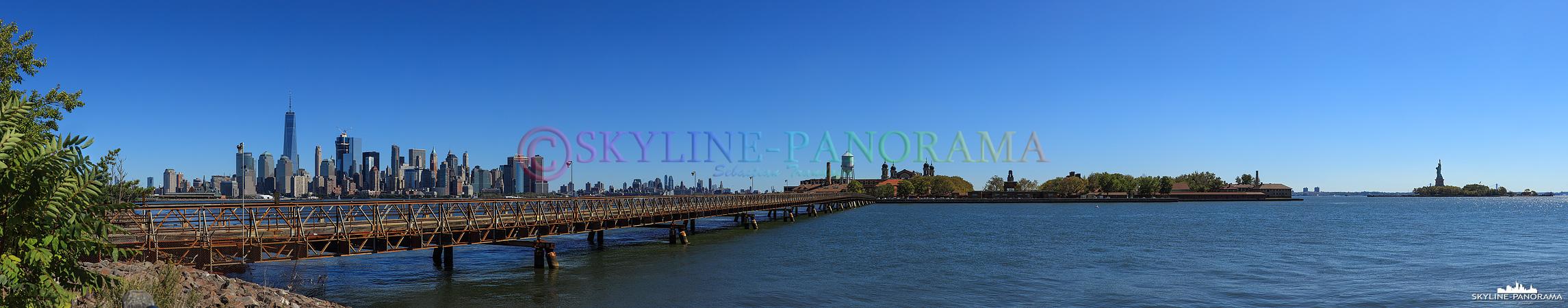 New York Skyline - Der Blick als Panorama von der Skyline Manhattans über Ellis Island zur Freiheitsstatue.