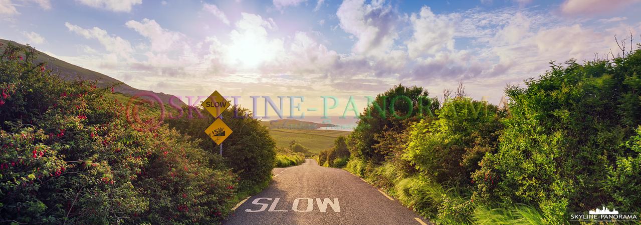 6x17 Panorama - Landstraße auf Valentia Island im Gegenlicht - der Hinweis zum langsamen Fahren ist bei den oft schmalen Straßen in Irland meistens angebracht.