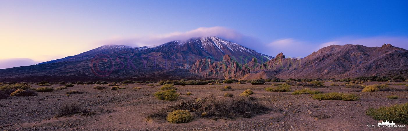 Zur Dämmerung unterwegs auf dem Teide Plateau. Der schneebedeckte Gipfel des El Teide leuchtet bei diesem Panorama im letzten Licht der untergehenden Sonne.