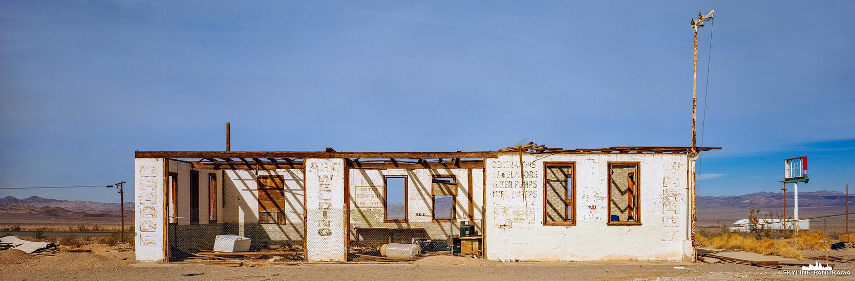 Route 66 Panorama - Eine verfallene Service Garage im Ghost Town Ludlow an der historischen Route 66 in Kalifornien. Die in den 1960er Jahren gebaute Interstate 40, machte das Befahren der Route 66 an dieser Stelle für den Verkehr unattraktiv, wodurch viele Orte dem Verfall überlassen wurden und bis heute als Erinnerung an diese Zeit in der Wüstenlandschaft zu sehen sind. Ebenfalls im Ghost Town Ludlow findet man eine verlassene iconic Route 66 Gas Station.