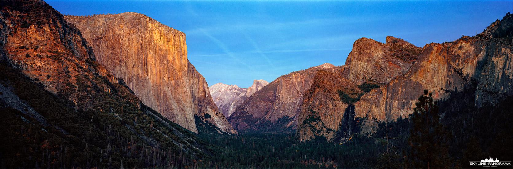 6x17 Panorama USA - Ein Ausblick zum Sonnenuntergang in das beeindruckende Valley des Yosemite National Park von einem der beliebtesten Aussichtspunkte aus, dem Tunnel View Poin. Die Letzten Sonnenstrahlen erleuchten die beiden bekanntesten Gipfel des Yosemite Nationalparks, rechts den El Capitan, mit seiner fast 1000 Meter hohen Felswand und dem Halfdome, am anderen Ende des Yosemite-Tals.
