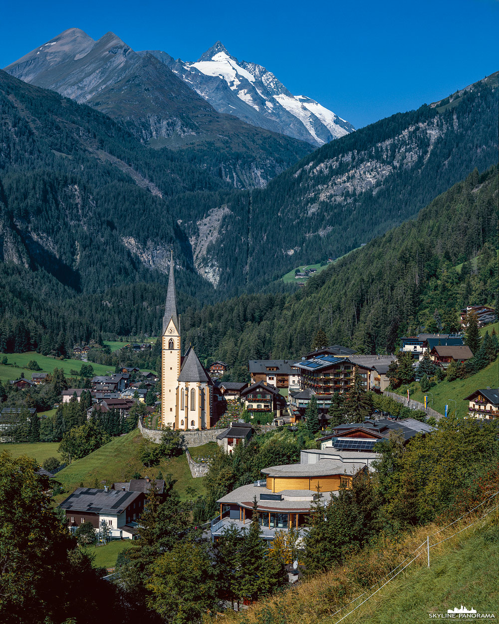 Die Gemeinde Heiligenblut mit dem beeindruckenden Blick zum Großglockner, dem höchsten Gipfel der österreichischen Alpen. Die Wallfahrtskirchen von Heiligenblut gehört zu den schönsten Sehenswürdigkeiten von Kärnten und ist auf vielen Postkarten aus der Region abgebildet.