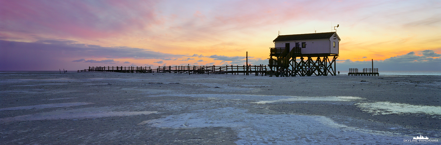 Nordsee-Motive - Der Strand von Sankt Peter-Ording im Winter als Panorama zum Sonnenuntergang . Zu dieser Jahreszeit und bei eisigen Temperaturen, trifft man am Strand, bei den bekannten Pfahlbauten, nur wenige Urlauber.