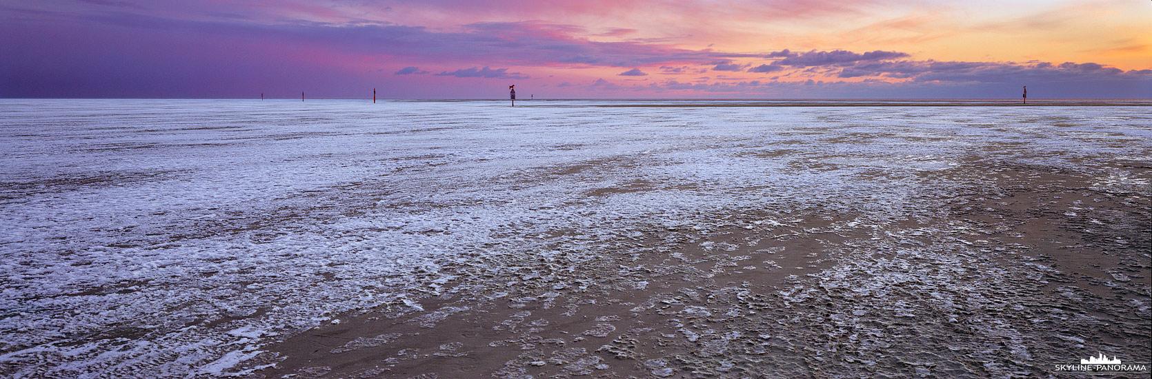 Panorama Nordseeküste - Der bis zum Horizont vereiste Strand von Sankt Peter-Ording zum Sonnenuntergang im Winter 2021.