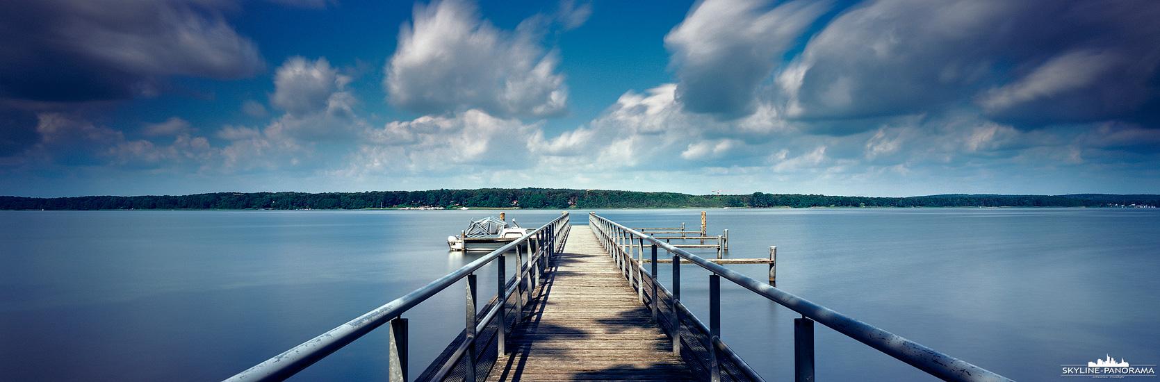 Der Scharmützelsee bei Bad Saarow in Brandenburg wird oft als märkisches Meer bezeichnet. Dieses Panorama eines Bootsstegs ist mit einer etwas längeren Belichtungszeit - in diesem Fall etwas über 2 Minuten - aufgenommen, wodurch sich die Wolken in Ihrer Bewegung abzeichnen und die Oberfläche des Sees glatt erscheint.