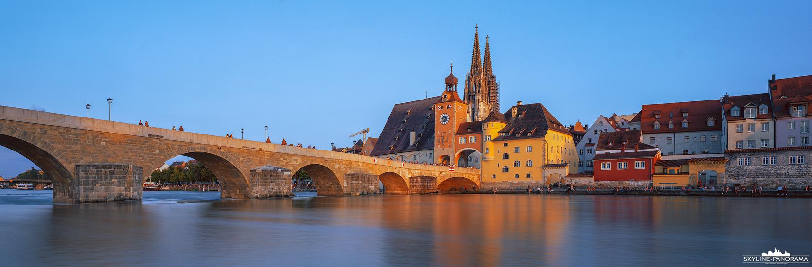 Die Altstadtansicht von Regensburg mit dem Regensburger Dom St. Peter, als bekanntestes Bauwerk der Stadt, und der Steinernen Brücke über der Donau. Das Panorama entstand zum Sonnenuntergang, wodurch die Fassaden in warmes Sonnenlicht getaucht sind.